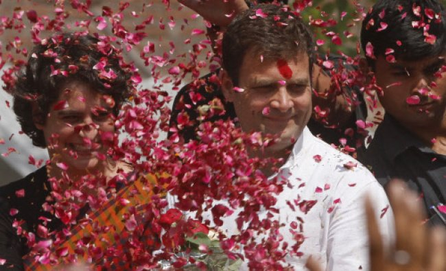 Rahul Gandhi and his sister Priyanka Vadra are showered with flower petals by supporters...