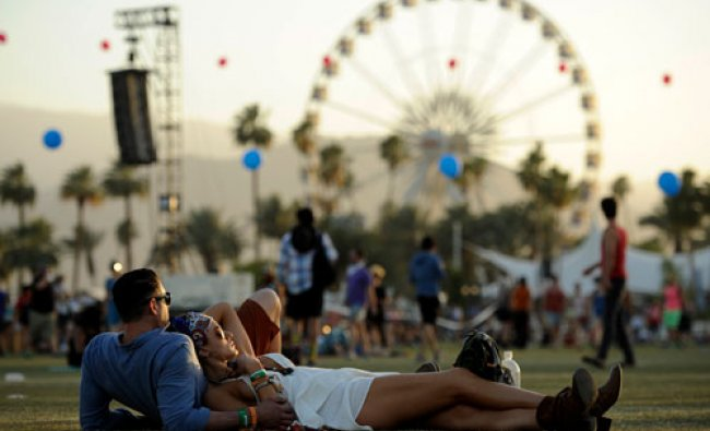 Coachella festivalgoers Justin Gibbs and Olivia Hansen of Los Angeles relax on the Empire Polo...