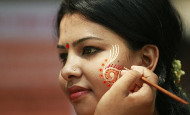 An artist paint the face of a woman as they celebrate Pohela Boishakh, the first day of the...