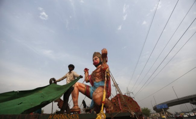 A labourer places a carpet on a trailer next to an idol of the Hindu monkey god Hanuman...