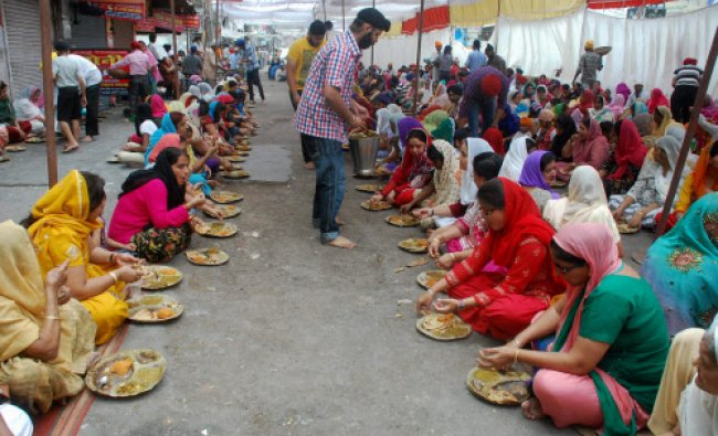 Devotees having \'langar\' on the occasion of Baisakhi festival in Lucknow...