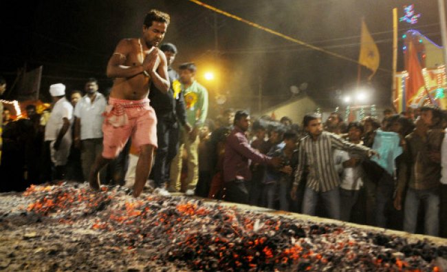 A tribal man walks on burning coals to pay tribute to the Lord Shiva during Manda festival...