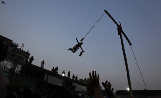 A devotee hangs from a rope during the \'Chadak\' ritual in Kolkata...