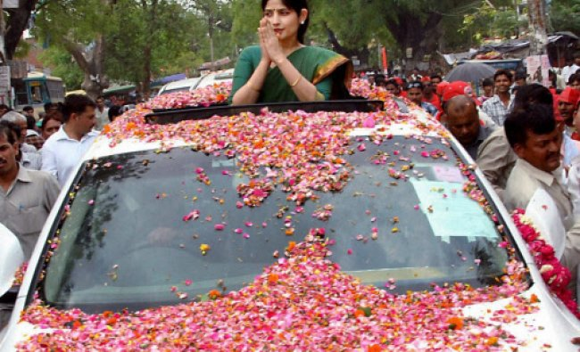 Supporters shower flower petals on Samajwadi Party candidiate Dimple Yadav during a road...