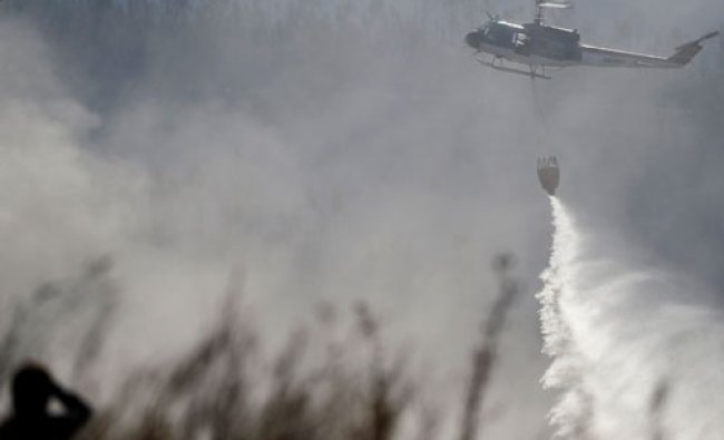 A helicopter dumps sea water on smoldering brush and debris after a fire burned several...