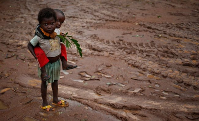 Children stand during rain in front of Saint Michel Catholic church in the town of Boda April 14...