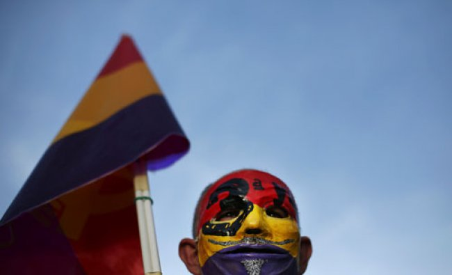 A demonstrator wears a mask with the colours of the Spanish Republican flag during a rally to...