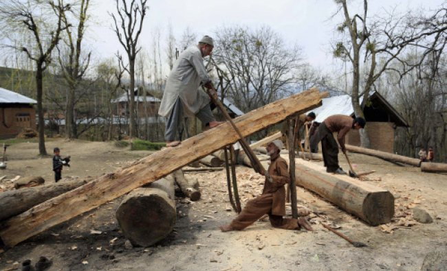Woodcutters use a handsaw to cut a cedar log in different sizes in Imam Sahib village...