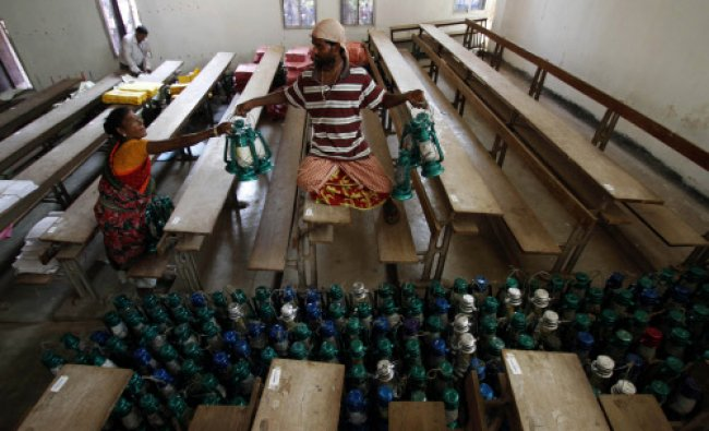 Daily wage laborers arrange lamps to be transported to respective election polling stations...