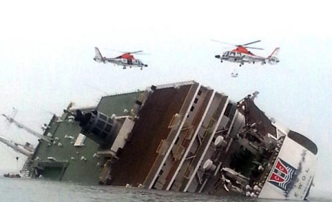 South Korean rescue helicopters fly over a South Korean passenger ship, trying to rescue ...