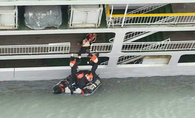 A passenger is rescued by South Korean maritime policemen from a sinking ship in the sea off ...