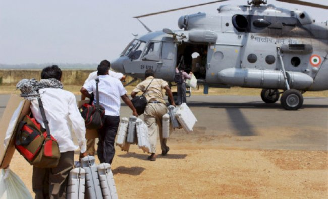 Polling officials board a chopper with Electronic Voting Machines for election duty in Naxal ...