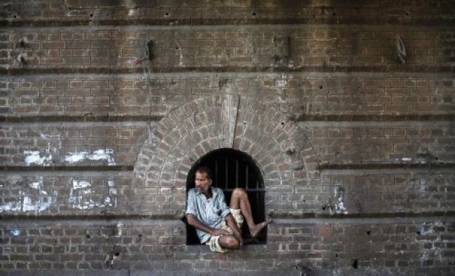 A labourer sits at a window under a railway bridge in the old quarters of Delhi...