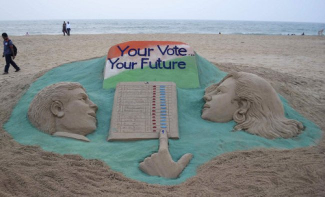 A visitor walks next to a sand sculpture on elections made by Indian sand artist Sudarshan...