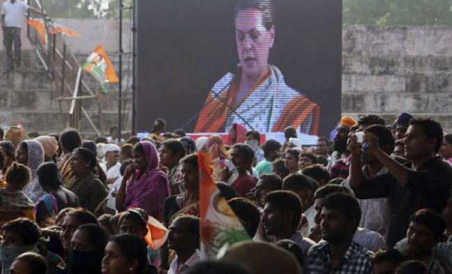 Congress party supporters listen to a speech by party president Sonia Gandhi, seen on a projector...