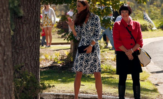 Catherine (L), Duchess of Cambridge, waves to residents as she walks with local official Miranda...