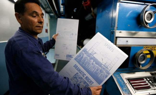 Printer Jose Lomeli holds newspaper printing plates for the first copies of the inaugural Los...