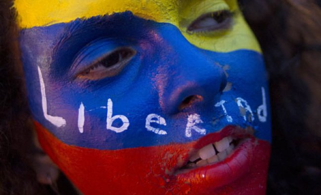 An anti-government protester with her face painted in the colors of Venezuela\'s flag with the...