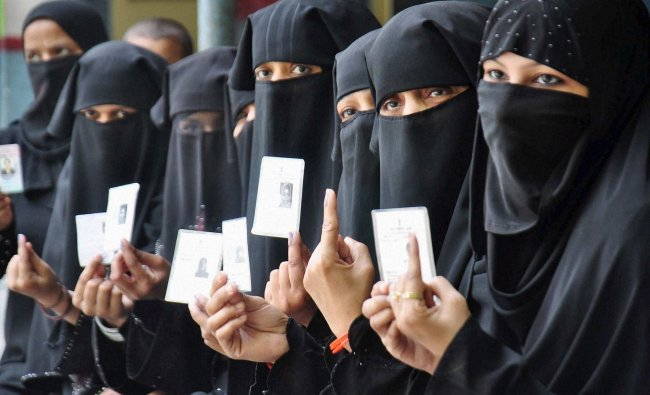 Muslim women show their inked fingers after casting votes for Lok Sabha elections in Moradabad on...