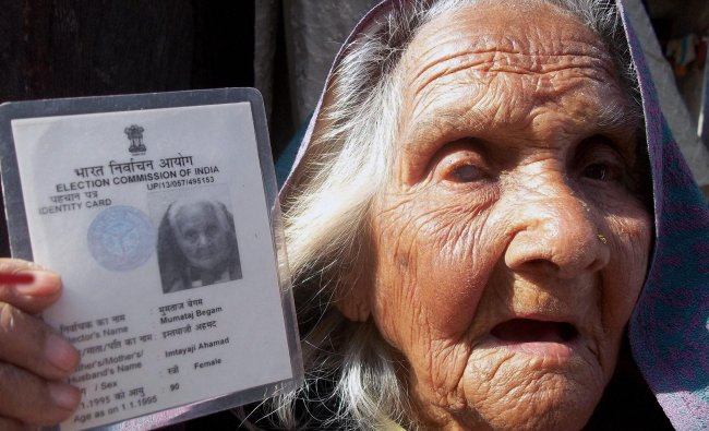 A 109-yr-old voter shows her identity card after casting her vote for Lok Sabha elections at a ...