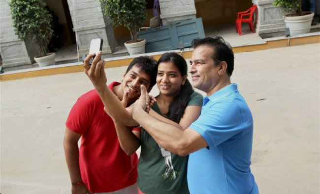 Voters click pictures of their inked fingers after casting votes for Lok Sabha polls at a ...