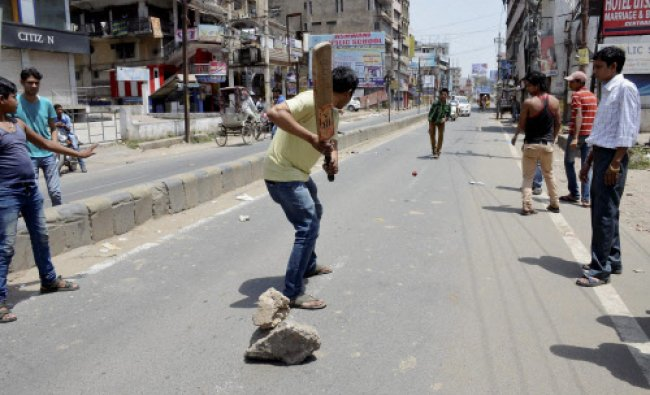 People play cricket on a road during voting for Lok Sabha polls in Patna...