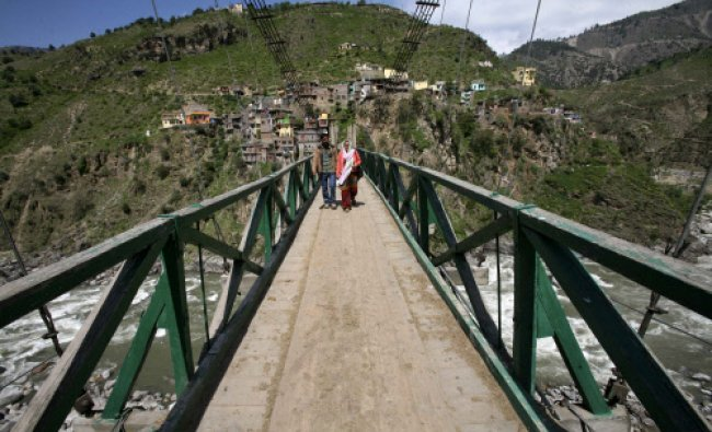 Voters cross a wooden bridge on the Chenab river to reach a polling station to cast their vote...