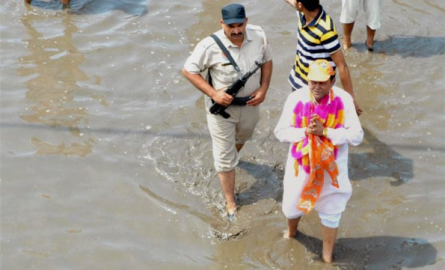 Shiv Sena candidate Harish Singla crossing a waterlogged road during his election campaign...