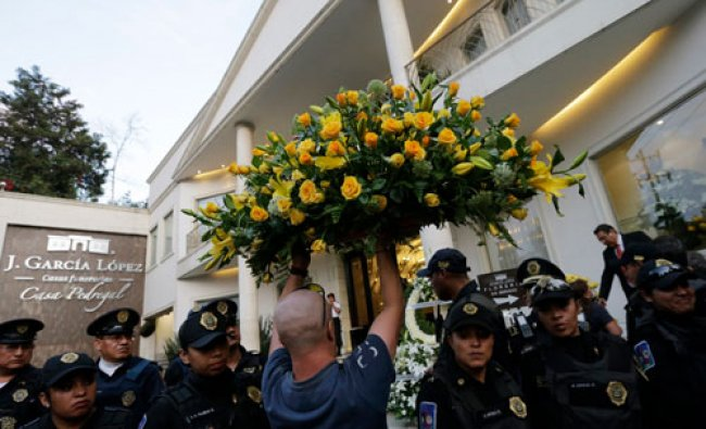 A man carries a flower wreath while passing through a line of police officers outside the funeral...
