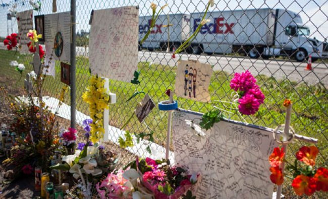 A FedEx truck drives past a makeshift memorial, set up in memory of those who died last week when...