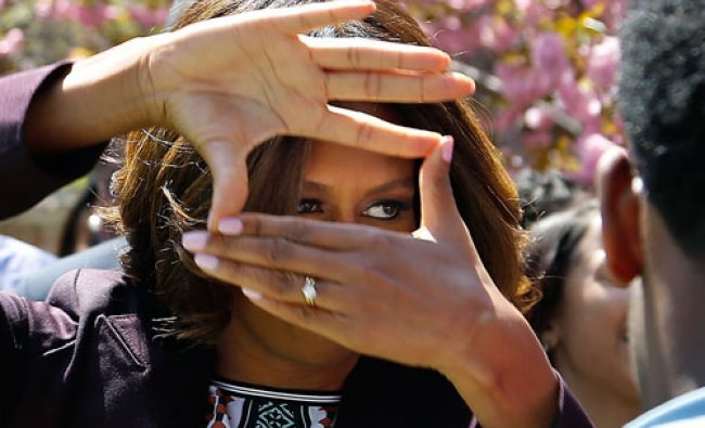 U.S. first lady Michelle Obama obliges cheering students by showing off the hand signal the...