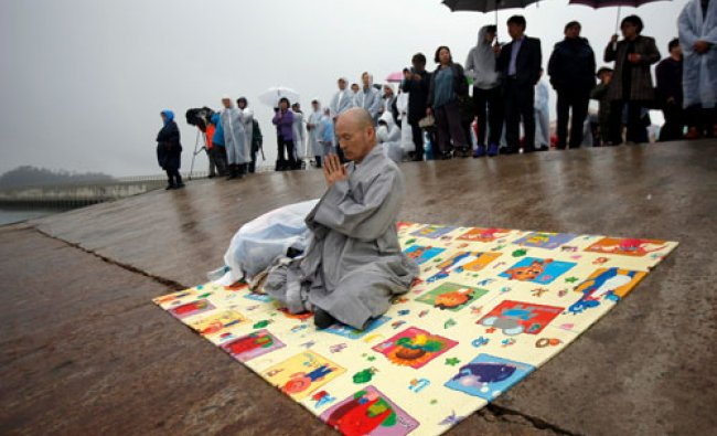 A Buddhist monk prays for missing passengers who were on the South Korean ferry \'Sewol\' which...