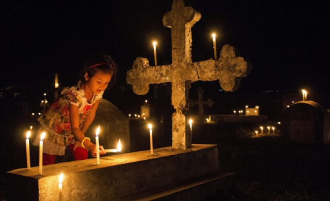 A girl lights a candle on a graveyard of Central baptist Church\'s central graveyard...