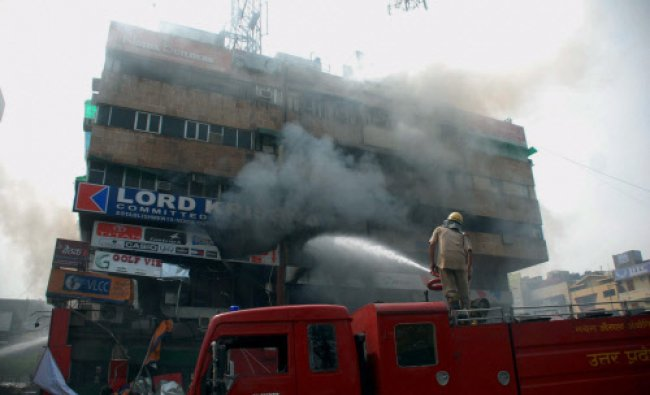 Fire fighters trying to douse a fire that broke out at a shopping complex in Noida...