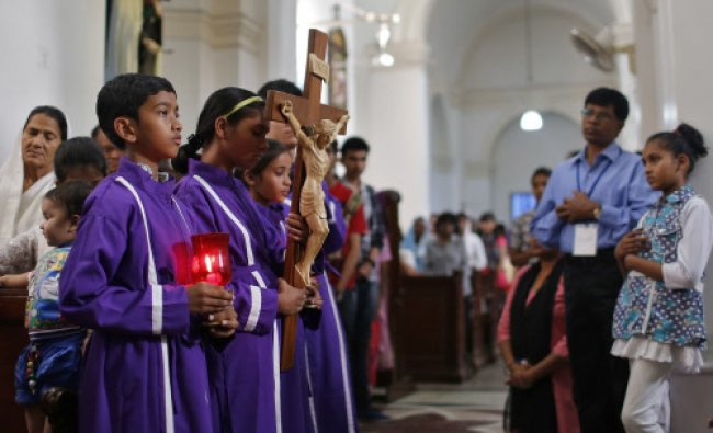 Catholic devotees attend a Good Friday Mass inside at a church in New Delhi...