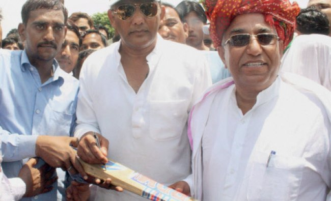 Congress candidate M Azharuddin gives autograph on bat during a public meeting in Tonk...