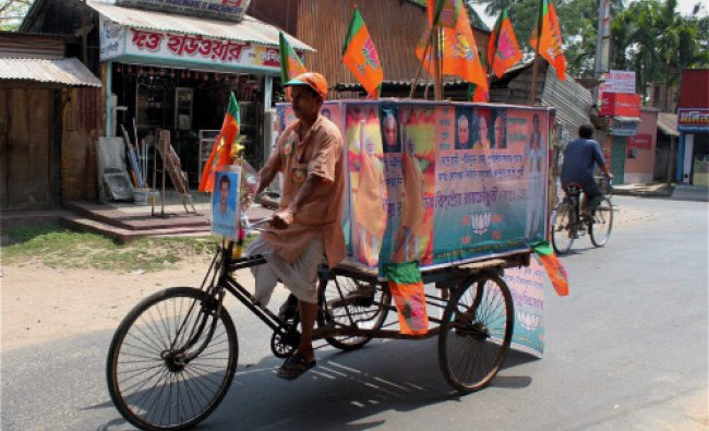 A BJP supporter campaigns with his decorated rickshaw at Balurghat in South Dinajpur...