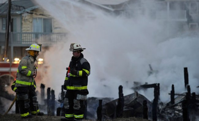 Firefighters stand near the remains of beachfront homes which caught fire in Sea Isle City, New...