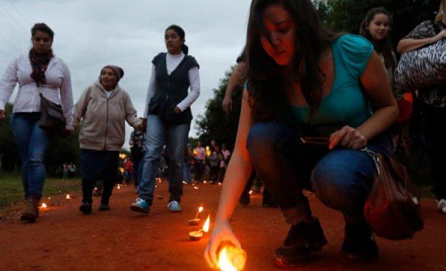 Pilgrims light candles held in orange skins on Good Friday in Tanarandy Mission April 18, 2014...