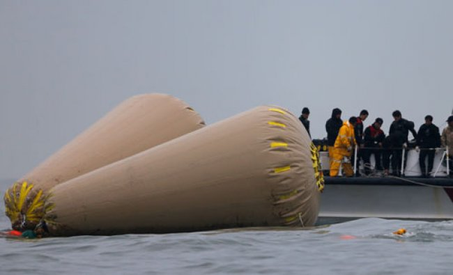 Rescue workers operate near floats where the capsized passenger ship \'Sewol\' sank, during the...