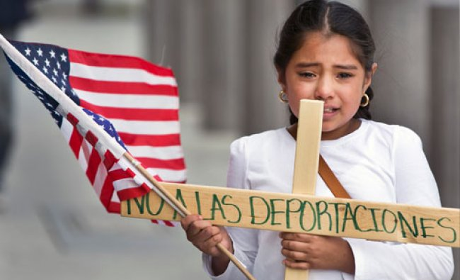 Yesenia Del Carmen 8, carries a cross reading \'No to the Deportations,\' \'as she and her...