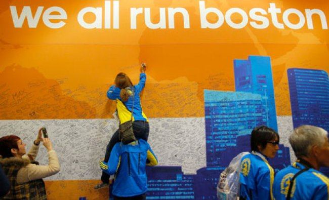 Runners, wearing jackets from the 2013 Boston Marathon, add their message to a cloth banner after...