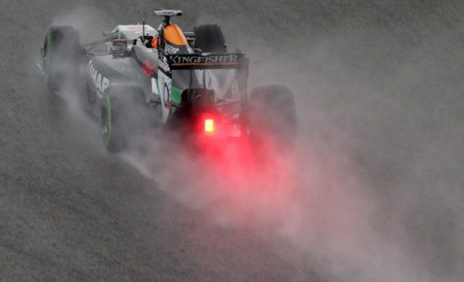 Force India driver Nico Hulkenberg drives in rain during the qualifying session of Chinese...