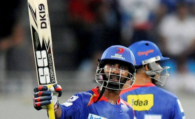 Dinesh Karthik of the Delhi Daredevils raises his bat after scoring a half century during...
