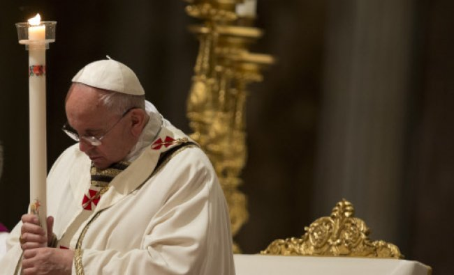 Pope Francis holds a tall, lit, white candle, as he leads the Easter vigil service ...