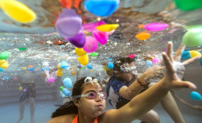 Ten-year olds Kaitlynn Tran of Chicago, and Michael Ramirez of Aurora, Ill., right, gather ...