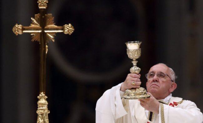 Pope Francis lifts up the chalice as he leads a vigil mass during Easter celebrations ...