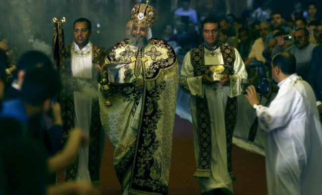 Coptic Pope Tawadros II, center, swings an incense burner as he walks down the aisle during...