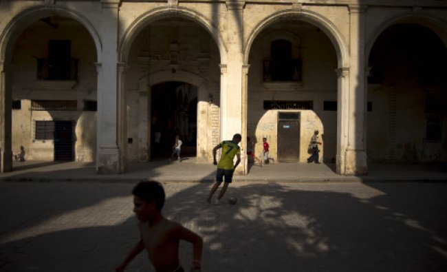 In this April 12, 2014 photo, children play soccer near a colonial building in Havana, Cuba.