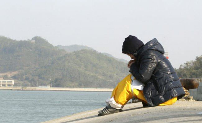A relative of a passenger aboard the sunken ferry Sewol prays as she waita for her missing loved ...